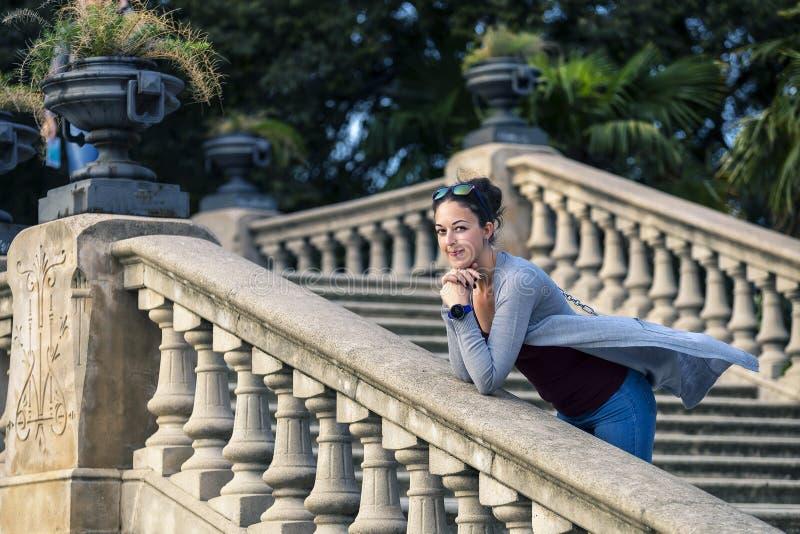 Porträt der jungen und attraktiven Frau in der grauen Jacke, die auf der Treppe steht lizenzfreie stockfotos