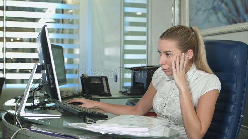 Porträt der jungen unglücklichen Geschäftsfrau am Schreibtisch im Büro lizenzfreies stockfoto