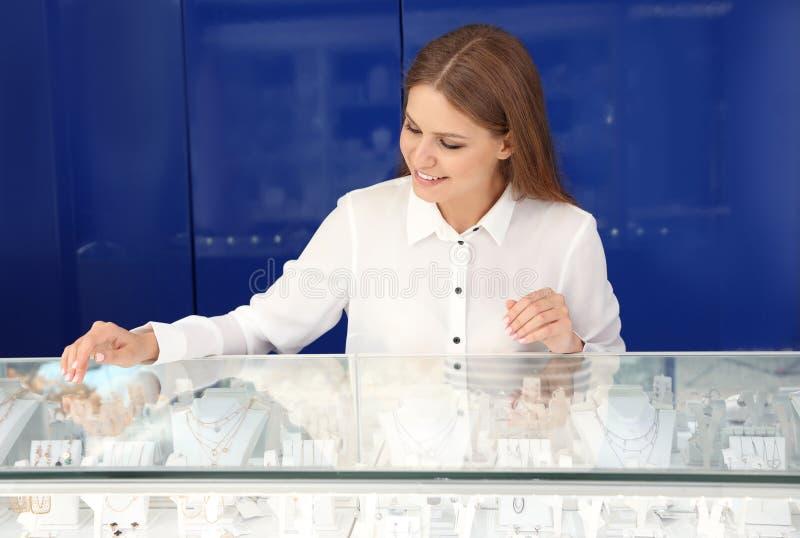 Porträt der jungen Verkäuferin nahe Schaukasten stockfotografie