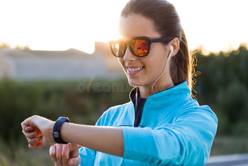 Porträt der jungen verwendenden Frau sie smartwatch nachdem dem Laufen stockfoto