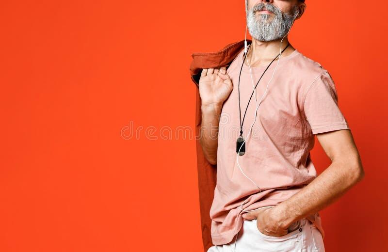 Porträt der kühlen, männlichen, modernen Holdinghand des alten Mannes in der Tasche, wegkamera in der Sonnenbrille schauend stockfotografie