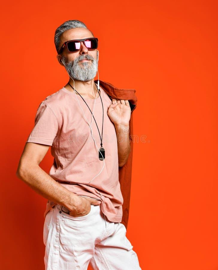 Porträt der kühlen, männlichen, modernen Holdinghand des alten Mannes in der Tasche, wegkamera in der Sonnenbrille schauend lizenzfreie stockfotos