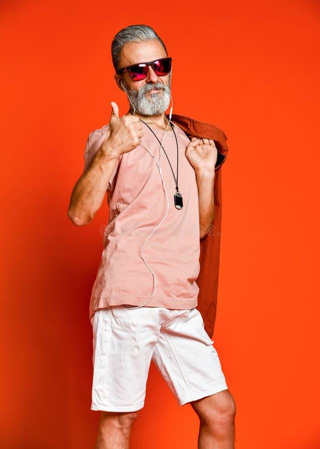 Porträt der kühlen, männlichen, modernen Holdinghand des alten Mannes in der Tasche, wegkamera in der Sonnenbrille schauend lizenzfreie stockfotografie
