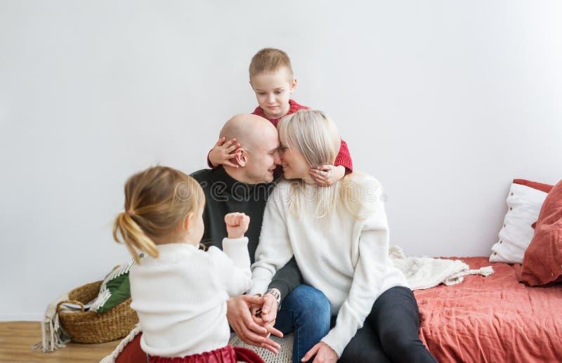 Porträt der küssenden Eltern und ihre kleinen Kinder, die zu Hause auf einem weichen Bett sitzen stockfotos