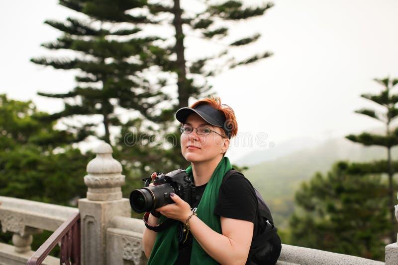 Porträt der kaukasischen Frau der glückseligen erwachsenen Rothaarigen in der zufälligen Kleidung mit ihrem Reflex-DSLR, das Foto lizenzfreies stockfoto