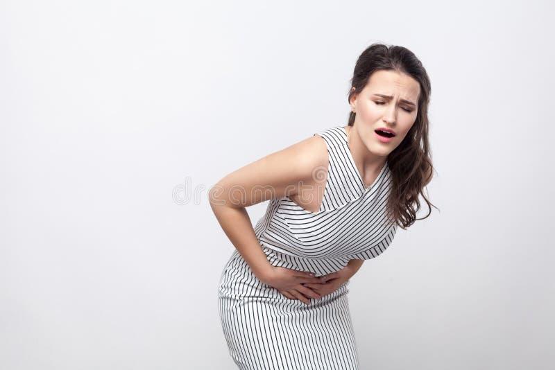 Porträt der kranken unglücklichen jungen brunette Frau mit Make-up und gestreifter Kleiderstellung mit Magenschmerzen und dem Hal stockbild