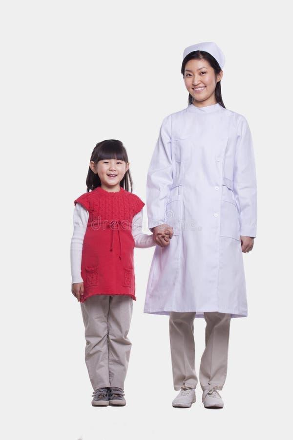 Porträt der Krankenschwester im Händchenhalten des einheitlichen und kleinen Mädchens, Atelieraufnahme lizenzfreie stockfotos