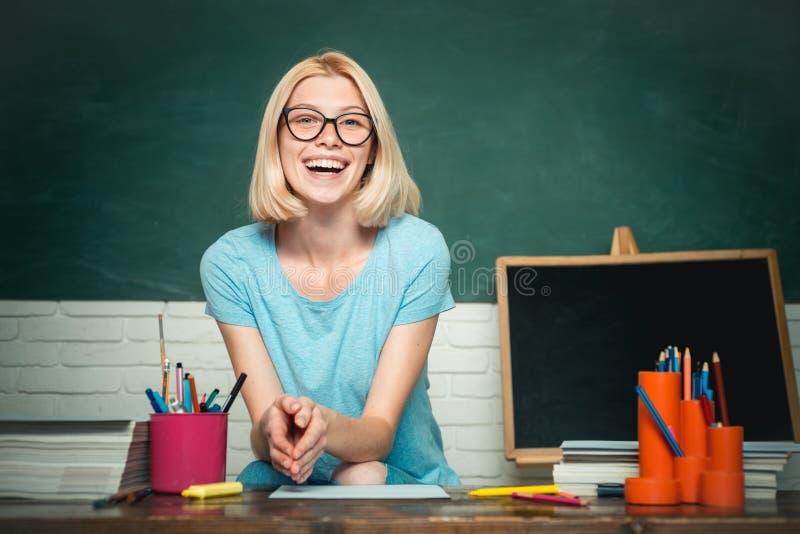 Porträt der kreativen jungen lächelnden Studentin in den Gläsern Lächelnde Studentin oder Lehrerinporträt auf Grün lizenzfreie stockbilder