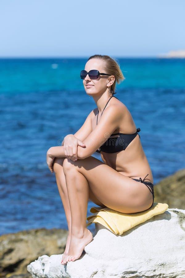 Porträt der kurzhaarigen gebräunten blonden Frau gegen Meer stockbild