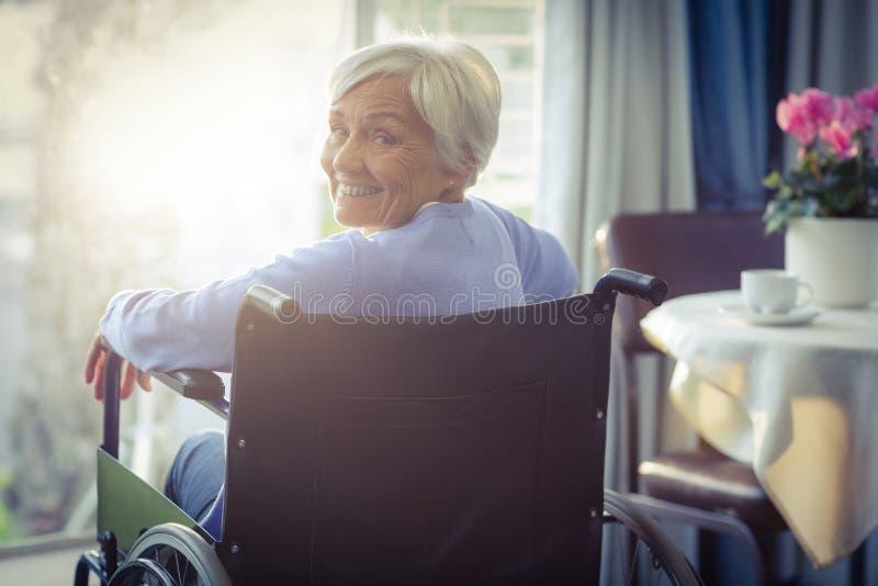 Porträt der lächelnden älteren Frau der älteren Frau, die auf Rollstuhl sitzt stockbilder