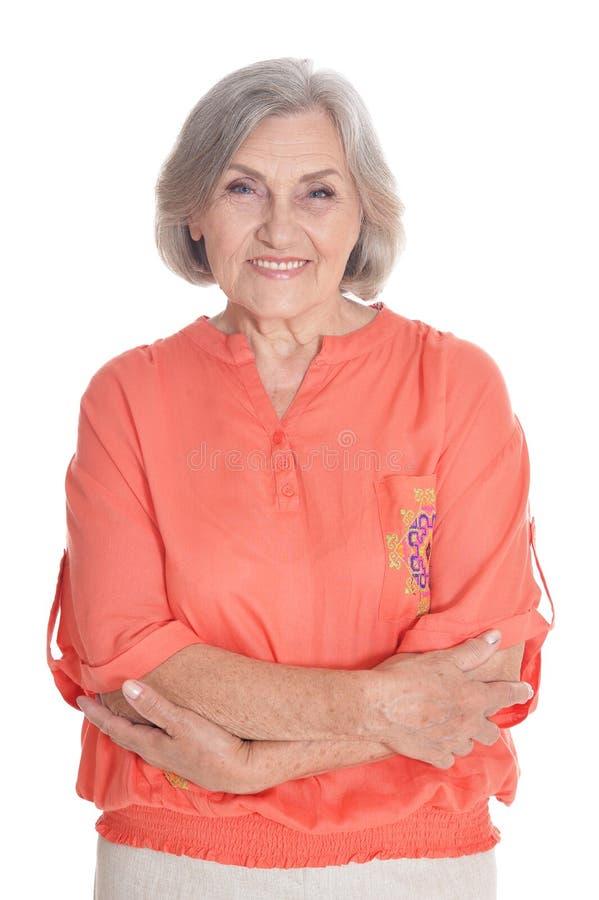 Porträt der lächelnden älteren Frau, die orange Bluse trägt lizenzfreie stockbilder
