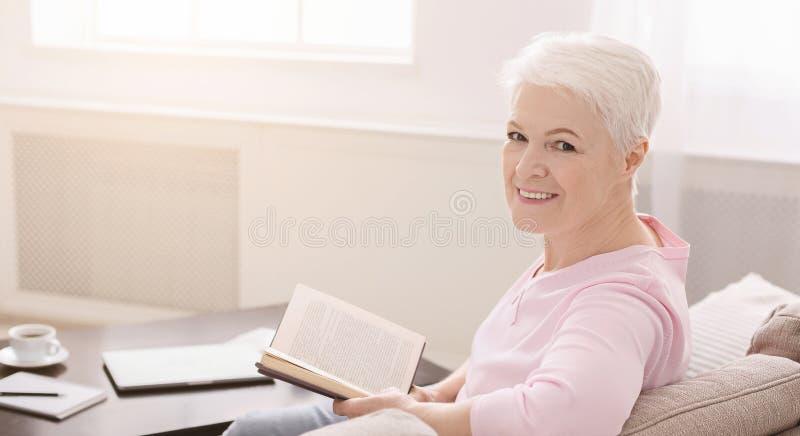 Porträt der lächelnden älteren Frau mit Buch auf Sofa zu Hause stockfotos
