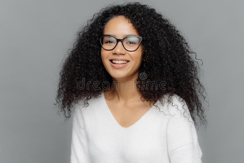 Porträt der lächelnden Afroamerikanerfrau trägt transparenten Eyewear und weißer Pullover, seiend in der Heiterkeit, drückt gutes stockbilder