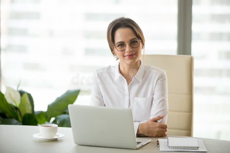 Porträt der lächelnden erfolgreichen Geschäftsfrau, die an Bürode aufwirft stockbild