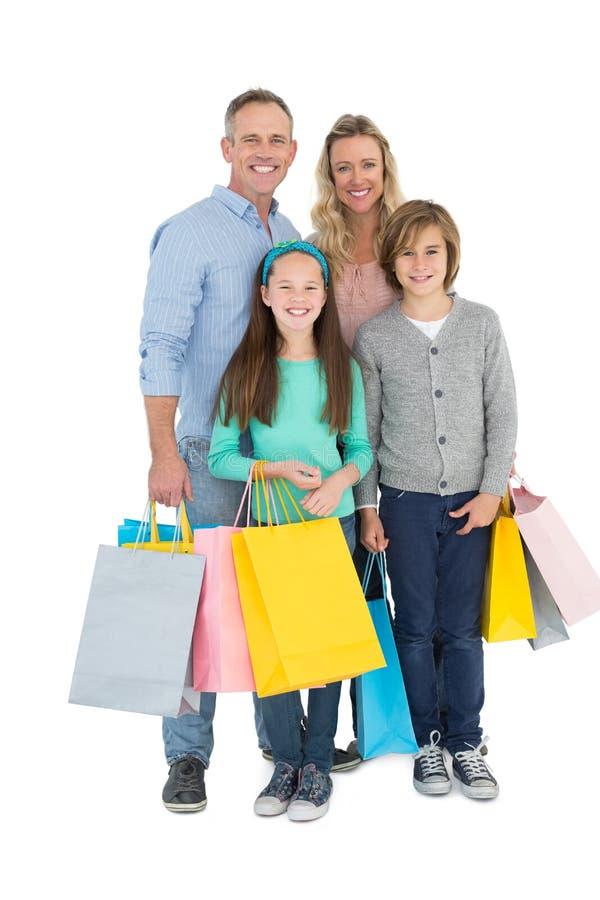 Porträt der lächelnden Familie mit Einkaufstasche stockfotografie