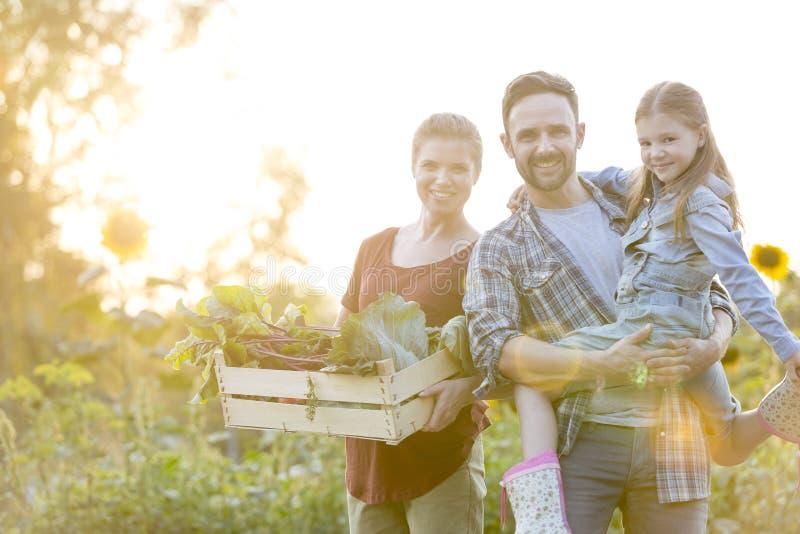 Porträt der lächelnden Familie mit Gemüse in der Kiste am Bauernhof stockfotografie