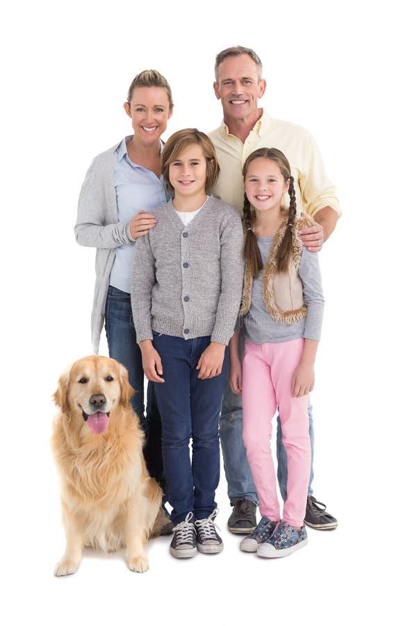 Porträt der lächelnden Familie stehend zusammen mit ihrem Hund lizenzfreie stockfotos