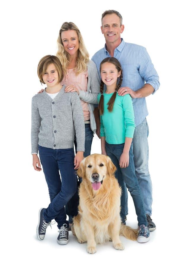 Porträt der lächelnden Familie stehend zusammen mit ihrem Hund stockfotos