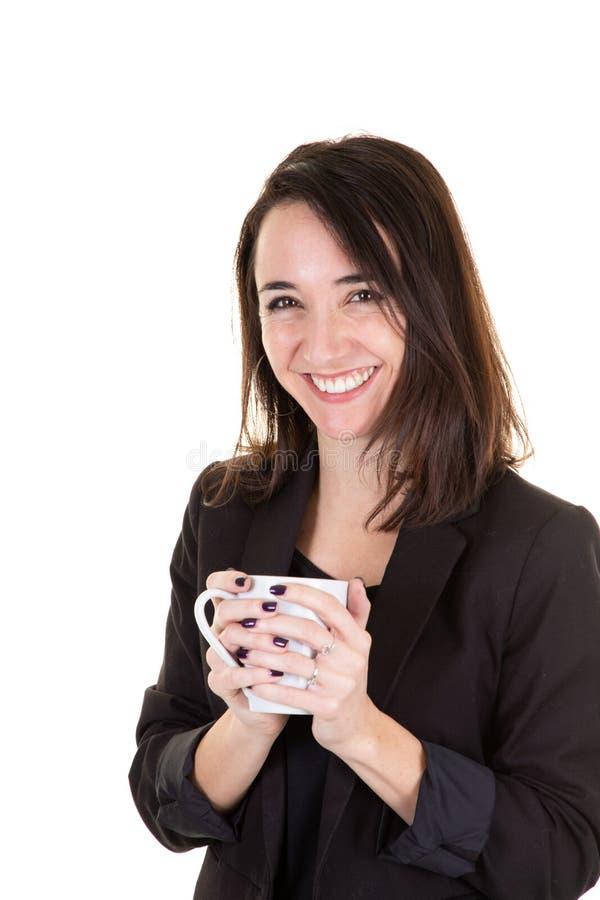 Porträt der lächelnden Frau eine Kaffeetasse halten, die sich zu Hause im weißen Wandwohnzimmer entspannt lizenzfreies stockbild