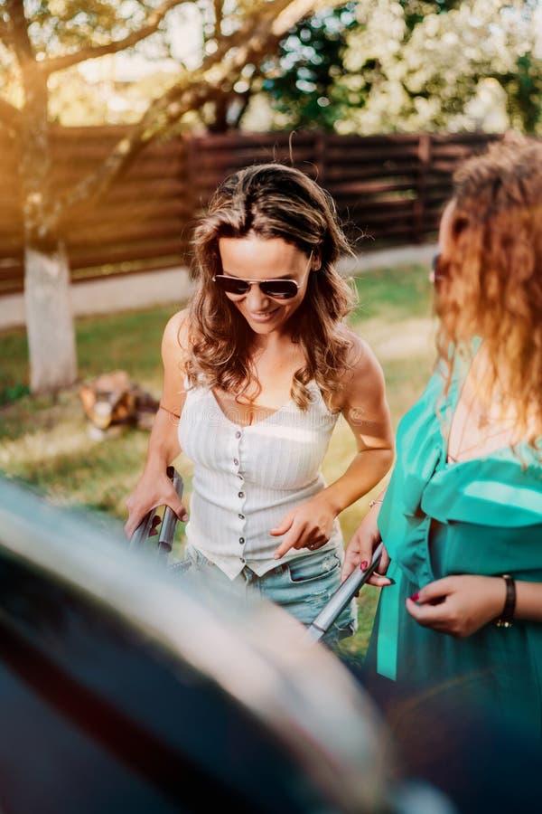 Porträt der lächelnden Frau kochend auf Grillgrill mit Freunden am Gartenfest stockfotografie