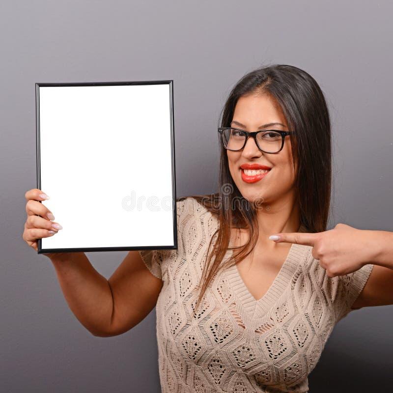 Porträt der lächelnden Frau leeren Fotorahmen gegen grauen Hintergrund halten stockfotografie
