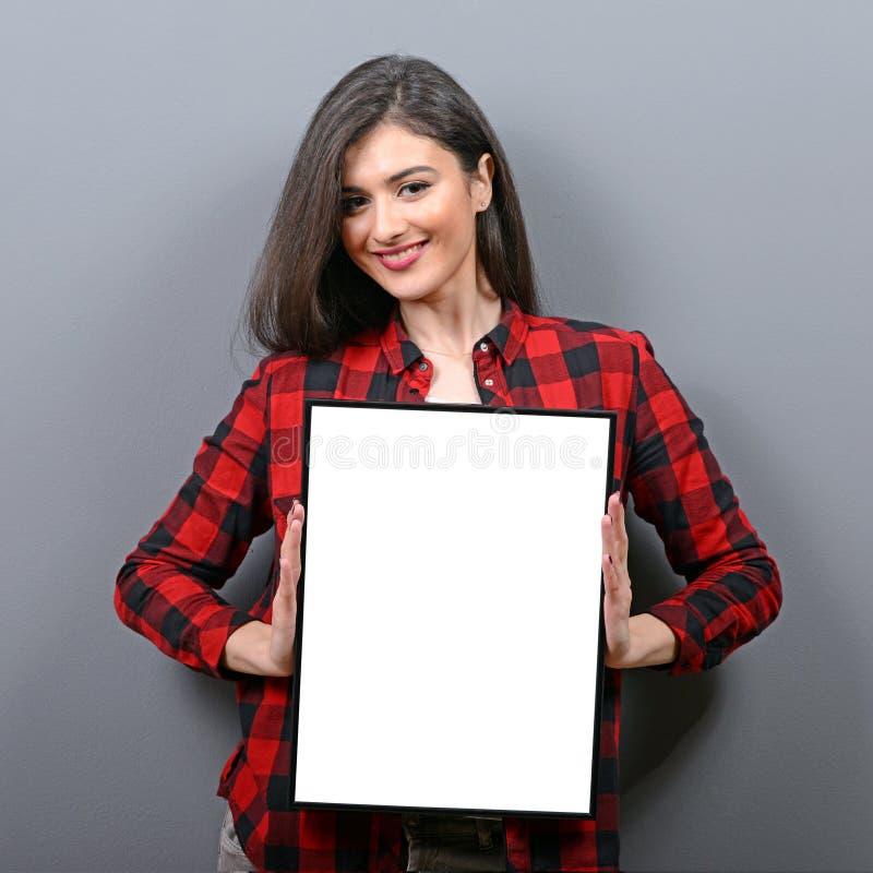 Porträt der lächelnden Frau leeres Zeichenbrett halten Studioporträt der jungen Frau mit Zeichenkarte gegen grauen Hintergrund stockfoto