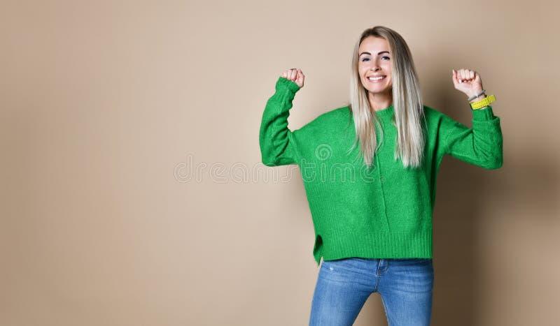 Porträt der lächelnden Frau mit den Fäusten oben gegen einen nackten Hintergrund stockbilder