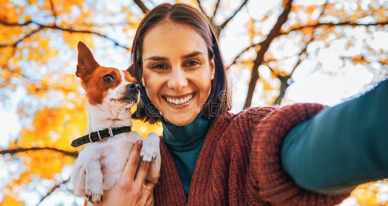 Porträt der lächelnden Frau mit Hund draußen im Herbst, der selfie macht stockfotos