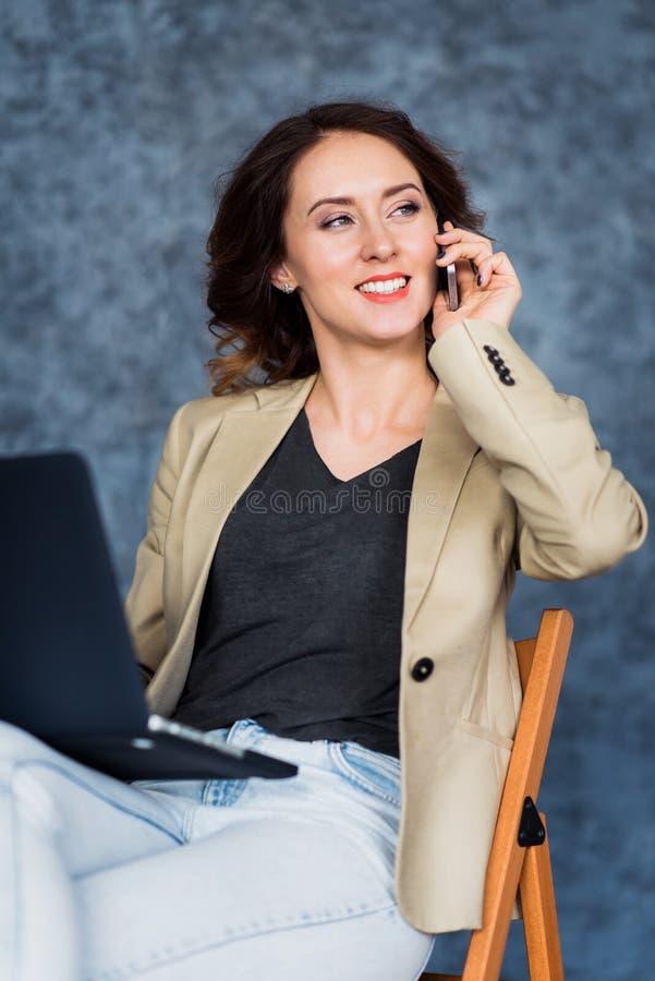 Porträt der lächelnden Frau sprechend auf Mobiltelefon mit dem Laptop, der auf ihren Knien liegt stockfotos