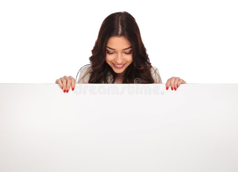Porträt der lächelnden Geschäftsfrau unten betrachtend leerem billboar stockfoto
