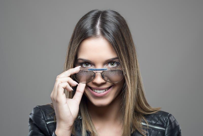 Porträt der lächelnden Grün gemusterten schönen jungen Frau, die Sonnenbrille hält, blicken auf Kamera flüchtig lizenzfreie stockfotos