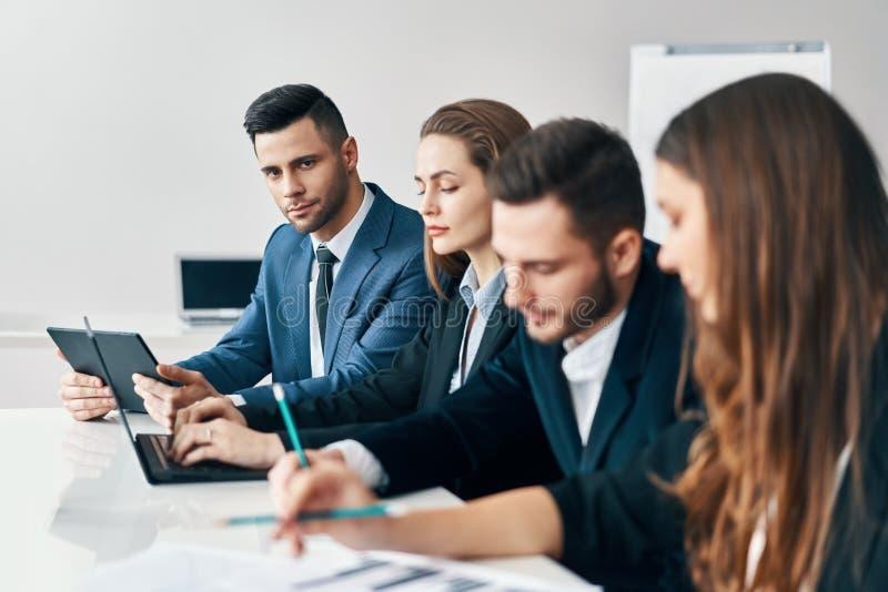 Porträt der lächelnden Gruppe Geschäftsleute, die in Folge zusammen bei Tisch in einem modernen Büro sitzen lizenzfreies stockbild