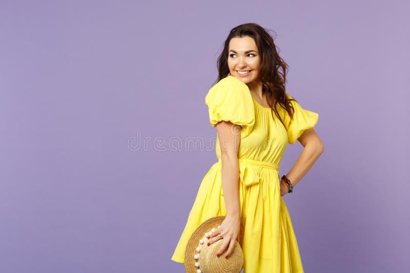 Porträt der lächelnden hübschen jungen Frau im gelben Kleid, das Sommerhut, schauend beiseite auf Pastellveilchen hält lokalisier stockbilder