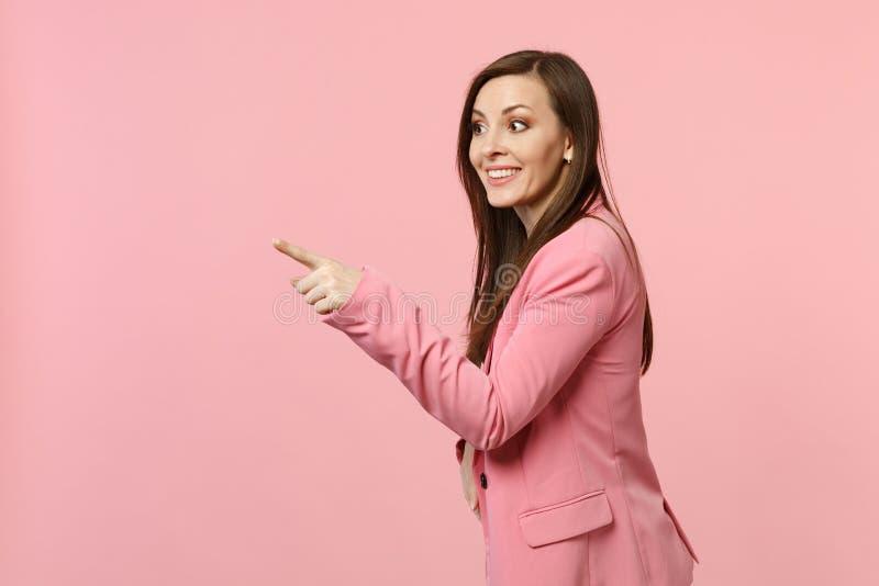 Porträt der lächelnden hübschen jungen Frau in der Jacke, die, Zeigefinger auf rosa Pastellwand beiseite zeigend schaut stockfoto