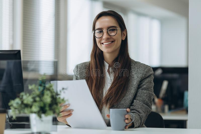 Porträt der lächelnden hübschen jungen Geschäftsfrau in den Gläsern, die auf Arbeitsplatz sitzen und mit Dokumenten arbeiten stockfotografie