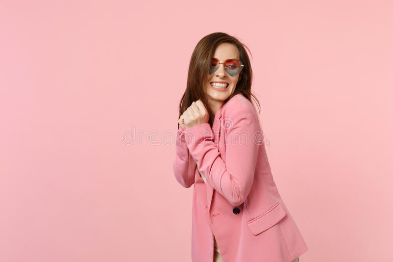 Porträt der lächelnden hübschen schönen jungen Frau in den Herzgläsern, die, schauend beiseite auf Pastellrosa stehen lokalisiert lizenzfreie stockbilder