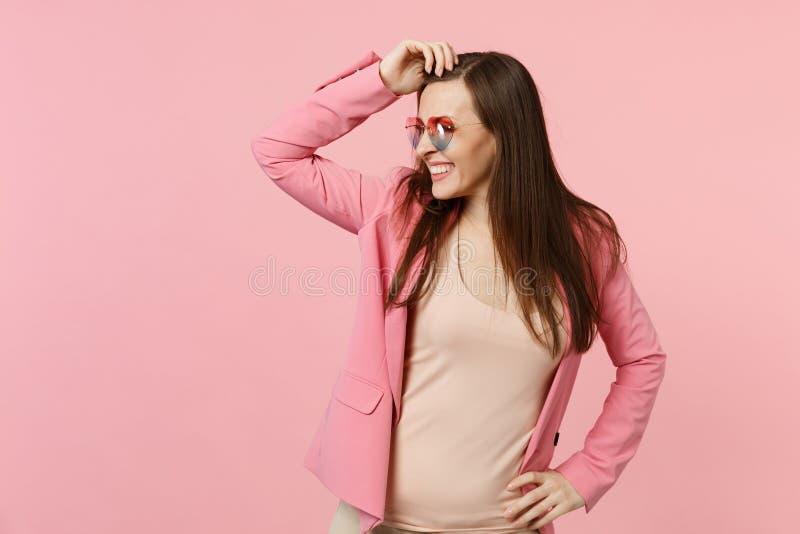 Porträt der lächelnden jungen Frau in den Herzgläsern, die Hand auf Kopf, schauend beiseite auf rosa Pastellwand setzen lokalisie lizenzfreies stockbild