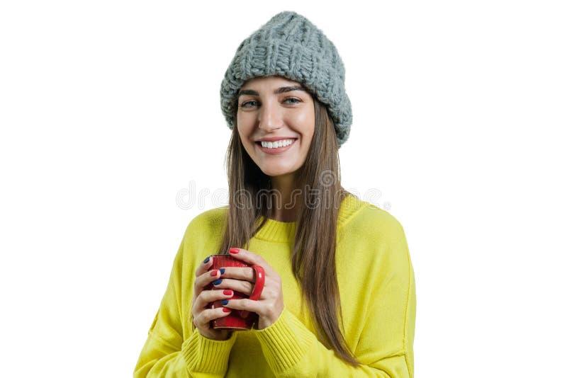 Porträt der lächelnden jungen Frau des Winters in der Strickmütze, gelbe Strickjacke mit der Schale des heißen Getränks, lokalisi stockfotografie