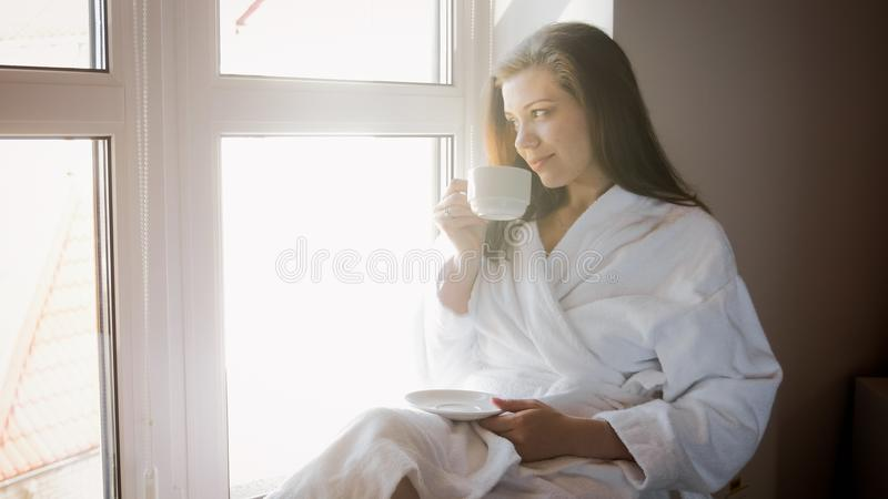 Porträt der lächelnden jungen Frau, die auf Fensterbrett und trinkendem Tee sitzt lizenzfreie stockfotografie