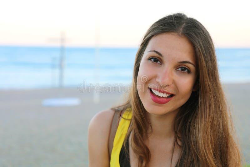 Porträt der lächelnden jungen Frau, die draußen zur Kamera auf dem Strand schaut lizenzfreies stockfoto