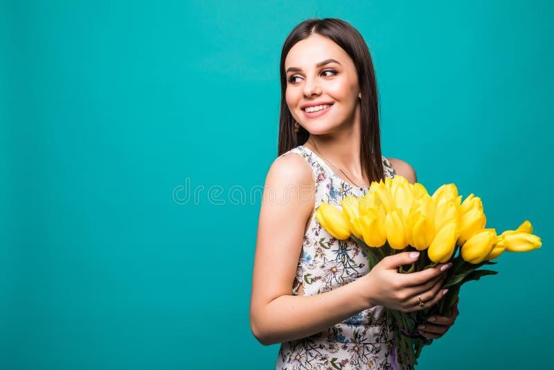 Porträt der lächelnden jungen Frau, die gelben Tulpenblumenstrauß lokalisiert über blauem Hintergrund hält lizenzfreies stockfoto