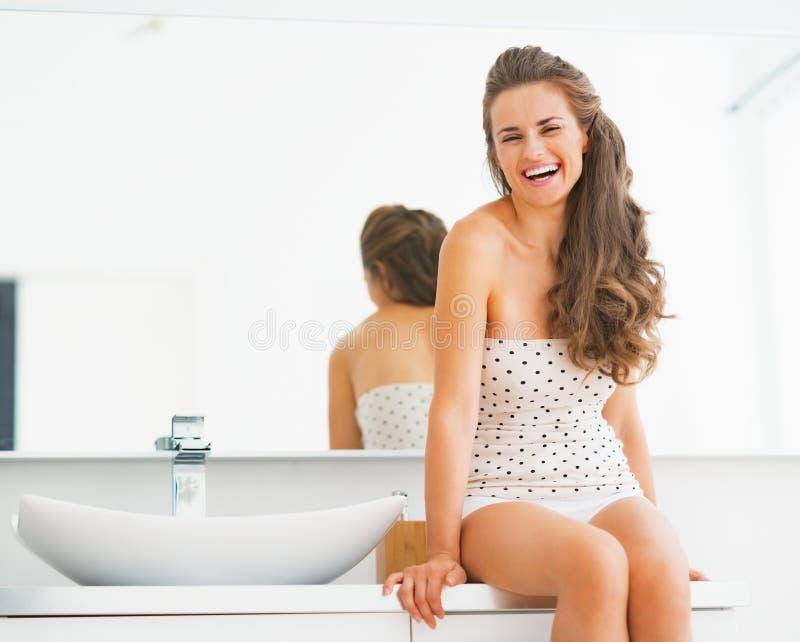 Porträt der lächelnden jungen Frau, die im Badezimmer sitzt stockfoto