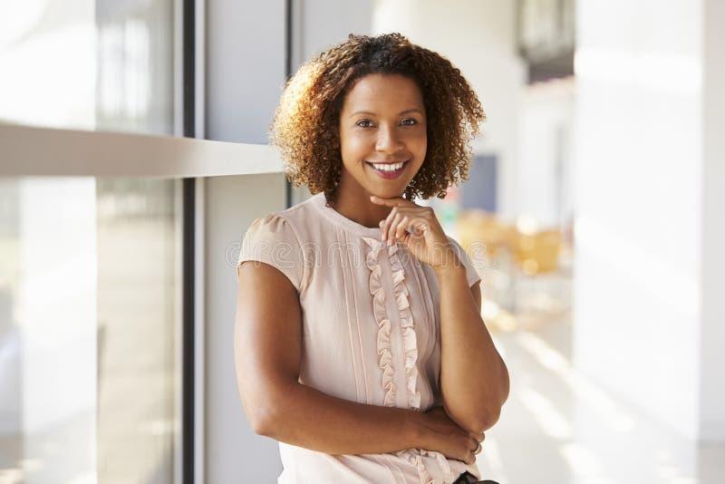 Porträt der lächelnden jungen Frau, die oben zur Kamera, Abschluss schaut stockbild