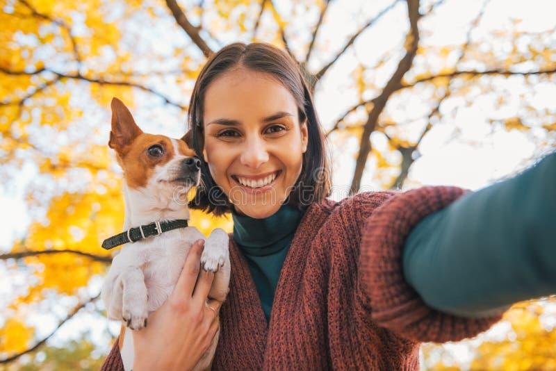 Porträt der lächelnden jungen Frau mit dem Hund, der selfie macht stockbild