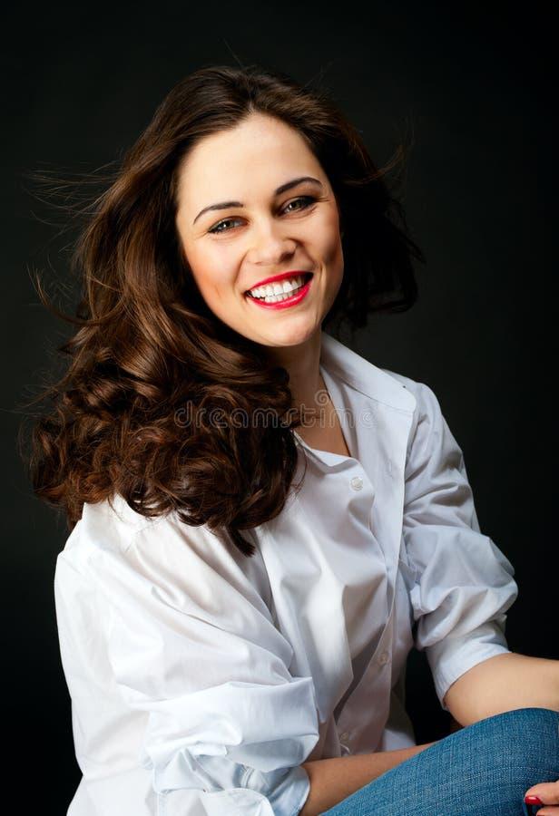 Porträt der lächelnden jungen Frau mit dem langen Haar in den Jeans und im Whit lizenzfreies stockfoto