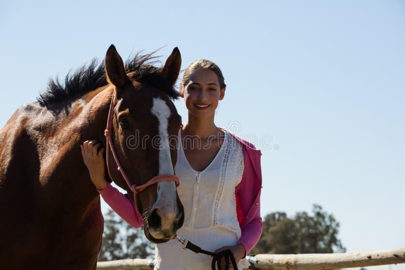 Porträt der lächelnden jungen Frau mit Pferd stockbilder