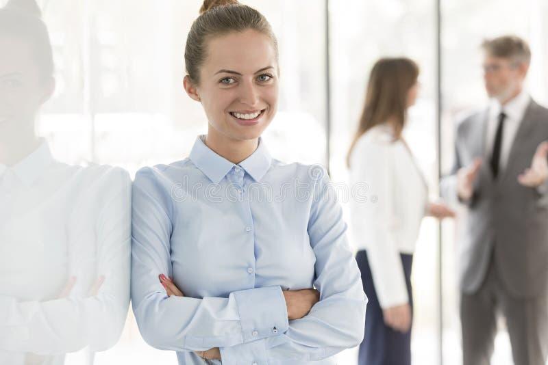 Porträt der lächelnden jungen Geschäftsfrau mit den Armen gekreuzt gegen Kollegen im Hintergrund stockbilder