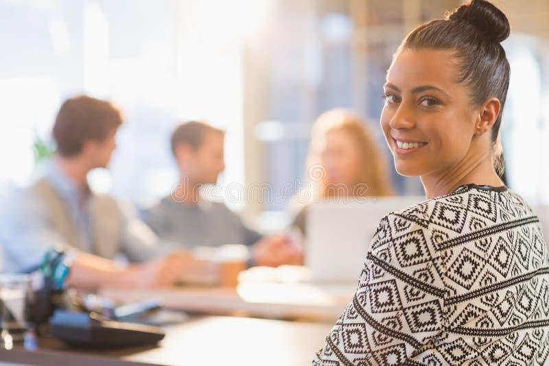 Porträt der lächelnden jungen Geschäftsfrau mit Kollegen lizenzfreies stockfoto