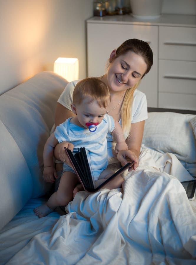 Porträt der lächelnden jungen Mutter, die Familienfotoalbum mit ihrem Baby betrachtet lizenzfreies stockbild