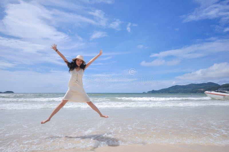 Porträt der lächelnden jungen Schönheit, die auf den Strand springt stockbilder